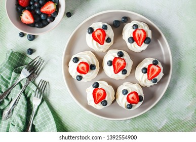 Mini Pavlova meringue with whipped cream and blueberries and strawberries, top view