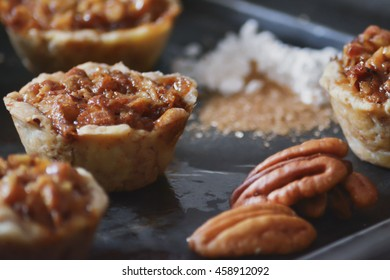 Mini pecan pies just out of the oven on a tray.