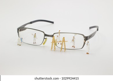a mini people worker cleaning eyes glasses.