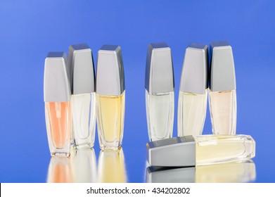 Mini perfume bottles on blue reflective surface