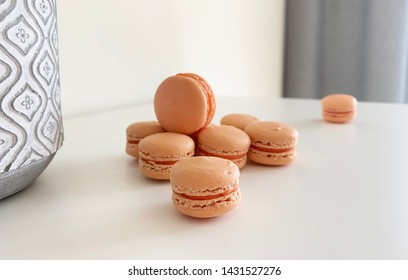 Mini pink french macarons on white table.