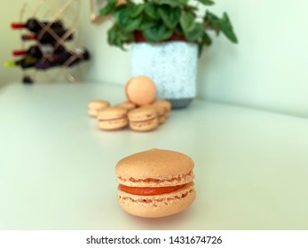 Mini pink french macarons. Wine bottles and flower in the background.