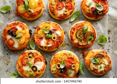 Mini pizzas with the addition various kinds of vegetables , mozzarella cheese and fresh basil on a on white baking paper, close-up, top view.