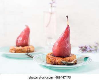 Mini polenta tartlets with pears in red wine sauce on green pastel plates with purple flowers on white and green pastel background