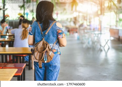Mini portable alcohol gel bottle to kill Corona Virus(Covid-19) hang on a leather shoulder bag of a woman wear a protective mask at a cafeteria. New normal lifestyle. Selective focus on alcohol gel