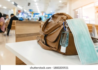 Mini portable alcohol gel bottle to kill Corona Virus(Covid-19) hang on a leather shoulder bag of a woman with a surgical mask on table at cafeteria.New normal lifestyle.Selective focus on alcohol gel