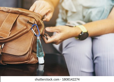 Mini portable alcohol gel bottle to kill Corona Virus(Covid-19) hang on a brown leather shoulder bag on table in coffee shop.New normal lifestyle. Health care concept. Selective focus on alcohol gel