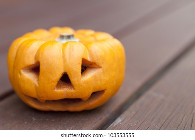 A mini pumpkin carved with a scary face for halloween