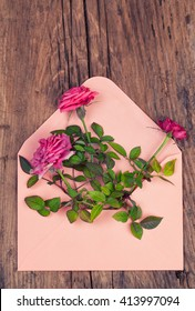 Mini rose flowers in a pink envelope on a vintage wood