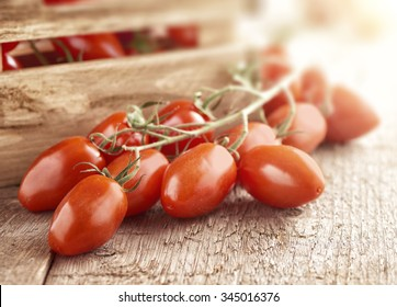 Mini san marzano tomatoes on the vine lying on a wooden surface in front of a small wooden crate full of ripe fresh tomaoes
