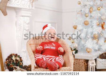 Mini Santa Claus Is Preparing For The Christmas Holidays. Santa Claus Sits  On A Chair