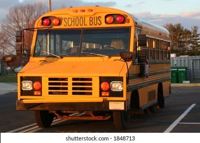 Mini school bus parked in school parking lot.
