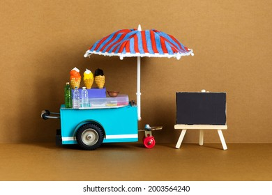 Mini shop Ice cream cart with blue red umbrella. Assortment of ice cream empty menu black chalkboard. Summer vacation concept. brown background.