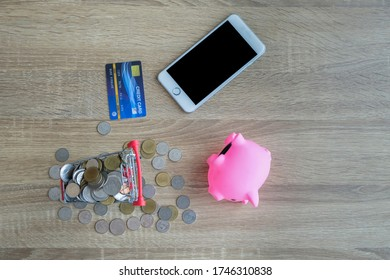 Mini shopping cart with a lot of coins with a pink piggy bank and mobile phone and mockup credit card. online shopping concept flat lay.