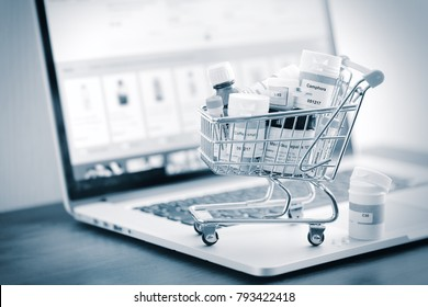 Mini shopping cart full of homeopathic remedies on laptop background. Homeopathy and internet online shopping concept. Black and white stylized.