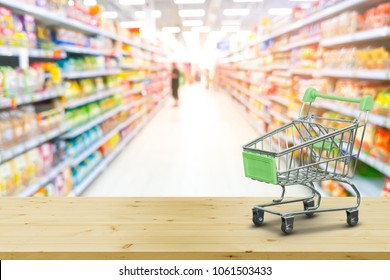 Mini Shopping Cart On wood with blur background supermarket shelves. Shopping online concept.