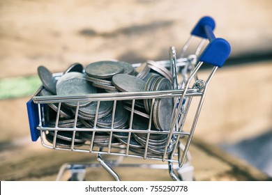 Mini shopping cart or supermarket trolley full of coins. Finance and savings concept