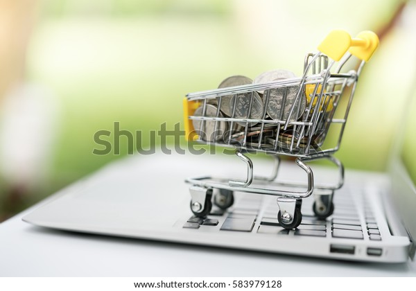 Mini shopping cart / trolley supermarket filled with coins on notebook using as e-commerce, saving, online shopping and business marketing technology concept.