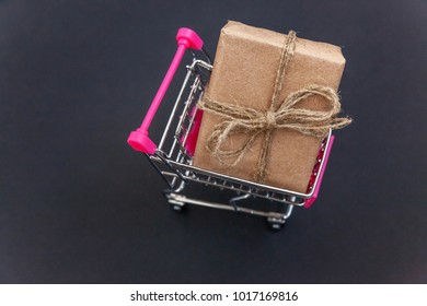 Mini shopping cart with vintage rustic gift box. Black background with copy space.