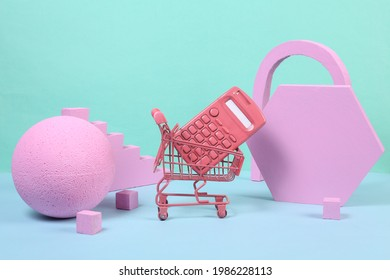 Mini shopping trolley with calculator and pink geometric shapas on blue background. Concept art. Minimalism. Creative layout