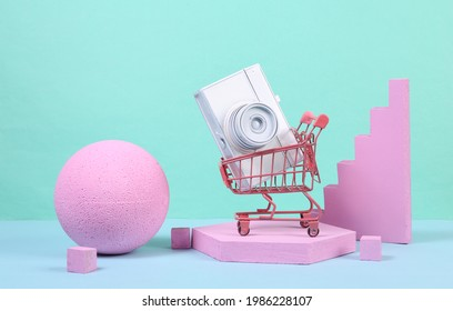 Mini shopping trolley with camera and pink geometric shapas on blue background. Concept art. Minimalism. Creative layout