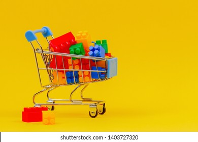 Mini shopping trolley cart full of colorful bricks on yellow background