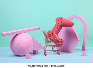 Mini shopping trolley with gamepad and pink geometric shapas on blue background. Concept art. Minimalism. Creative layout