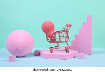 Mini shopping trolley with light bulb and pink geometric shapas on blue background. Concept art. Minimalism. Creative layout