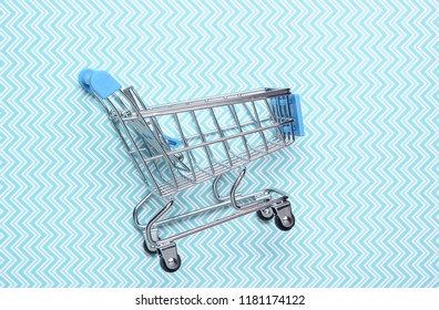 Mini shopping trolley for shopping on blue background, consumer concept, minimalism, top view.