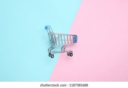 Mini shopping trolley for shopping on a colored pastel background, consumer concept, minimalism, top view.