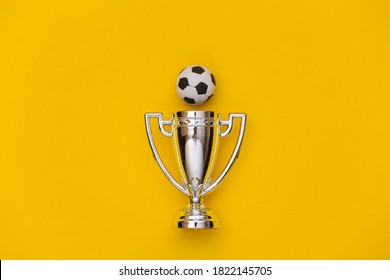 Mini soccer ball and champion cup on yellow background. Minimalism Sport concept. Top view. Flat lay