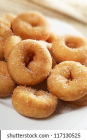 Mini sugar coated doughnuts piled on a white plate. Narrow dof