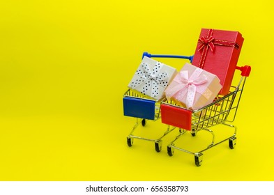 mini supermarket shopping cart red and blue color with mini colorful gift box on yellow background, holiday sale and shopping concept, selective focus, copy space