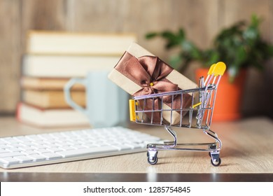 Mini supermarket trolley with gift box on the office desk with keyboard, alarm clock and cup.