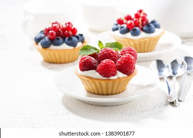 mini tarts with cream and berries on white table, horizontal