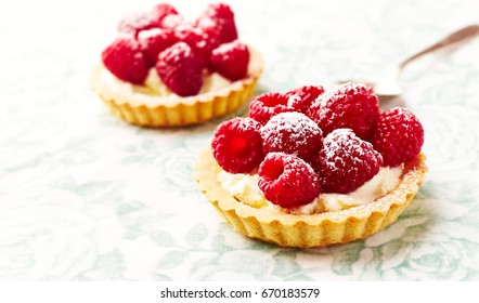 Mini Tarts with Mascarpone Cheese and Raspberries. Concept for a tasty sweet dessert. Bright background. Close up.