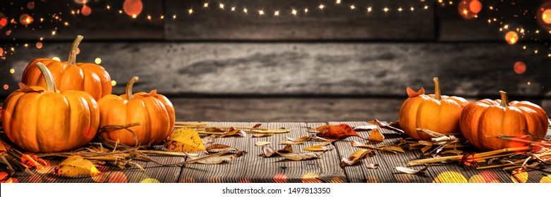 Mini Thanksgiving Pumpkins And Leaves On Rustic Wooden Table With Lights And Bokeh On Wood Background - Thanksgiving / Harvest Concept