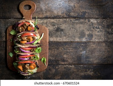 Mini tortilla sandwiches with ground meat and vegetables salad on wooden background with blank space