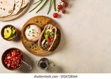 Mini tortillas with tomato salsa, avocado and boiled chicken. Top view.
