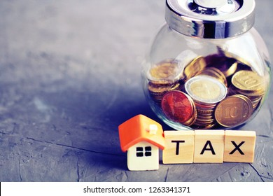 """Mini toy housу and wooden letters """"tax"""", money on the background. Selective focus. Property tax concept."""