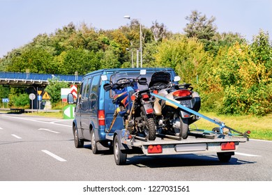 Mini van with motorcycles on trailer in Road in Slovenia.