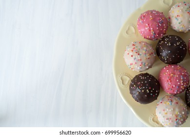 Mini Vanilla Cupcakes with Icing and Sprinkles on Plate from Above Copy Space Left