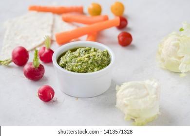 Mini vegetables served with pestos: avocado, hemp and pumpkin seeds pesto; almond, mint and basil pesto: walnut, kale and parsley pesto served with a silver spoon on light background.
