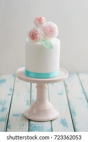 Mini white fondant covered wedding cake with wafer paper ranunculus flowers on pink cake stand with turquoise ribbon