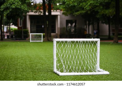 Mini white soccer or football goal on an artificial grass in a school.