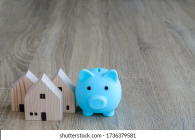 Mini wooden house and blue piggy bank on wood table, Saving money for home property concept.