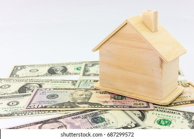 Mini wooden house and stethoscope on dollar banknote money with wood table background. Image for property real estate investment concept. (selective focus )