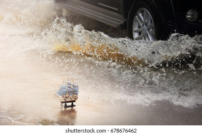 Mini wooden sailboat with motion car runs through flood and water splash during hard rain fall.