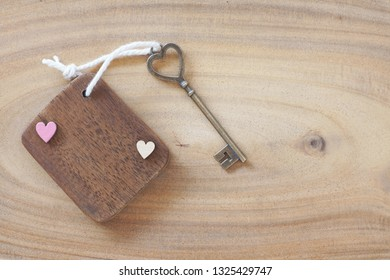 Mini wooden tag with beautiful antique heart shape key on wood background. Welcome to new home, home sweet home concept. Copy space.