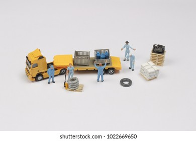 Mini worker and yellow lorry moving the goods